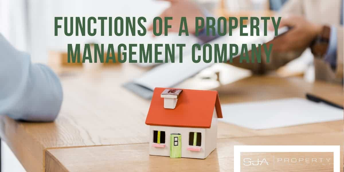 small model of a home sitting on a desk with partial and blurred background of two people reviewing documents. text overlay that reads, functions of a property management company